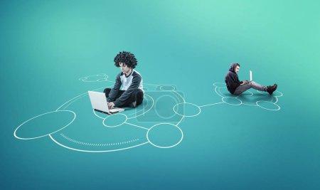Photo pour Deux hommes travaillant ensemble sur un ordinateur portable dans un réseau - image libre de droit