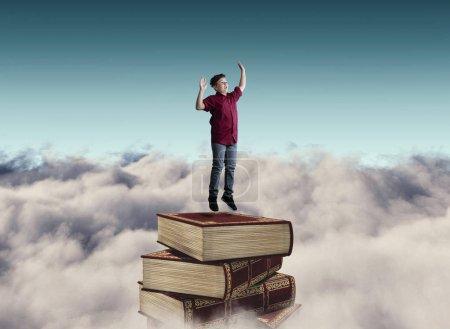 Photo pour Jeune homme sautant sur une pile de livres au-dessus des nuages - image libre de droit