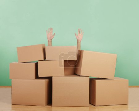 Photo for Hands raised behind cardboard boxes - Royalty Free Image