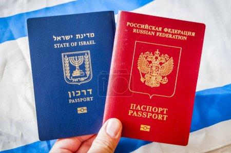 Photo pour Main tenant deux passeports étrangers: le passeport de l'Etat d'Israël et la Russie (Fédération de Russie), illustration de notion de double nationalité de passeport. - image libre de droit