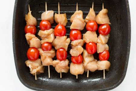 Raw chicken kebabs on grill pan, top view