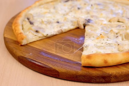 Photo for Pizza without one slice with mushrooms champignons and cheese on wooden board on the table. Close-up side view - Royalty Free Image