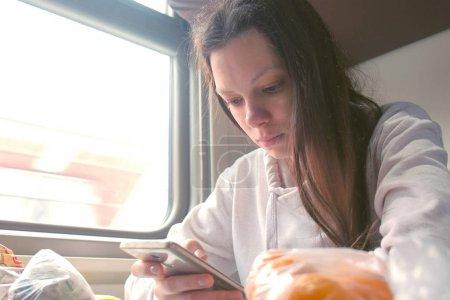 Mujer cansada está leyendo un libro en un smartphone viajando en un tren de larga distancia .