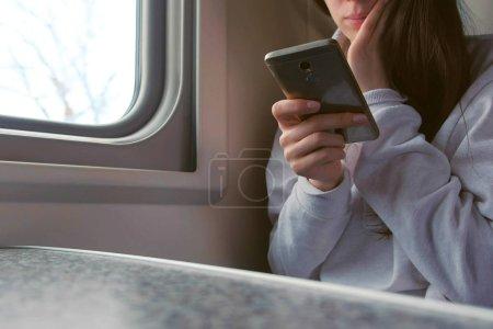 Mujer joven cansada en tren viendo vídeo en el teléfono móvil. Primer plano de las manos .