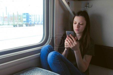 Mujer joven cansada en tren viendo vídeo en el teléfono móvil .