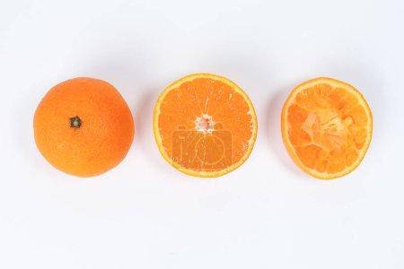 Photo pour Tranche de fruits orange mandarine moitié jus extrait sur fond blanc - image libre de droit