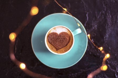 Coffee in a mint cup with a heart pattern and a gift wrapped