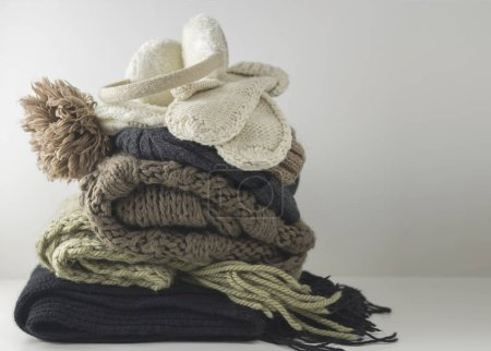 Photo for Warm woolen knitted winter and autumn clothes, folded in a pile on a white table. Sweaters, scarves, gloves, hat, headphones. Place for text. Copyspace - Royalty Free Image