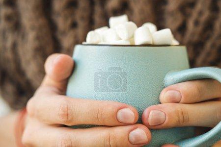 Photo pour Mug bleu avec café, chocolat chaud ou de chocolat avec guimauve en mains féminines. Concept d'automne agréable chaud ou en hiver - image libre de droit