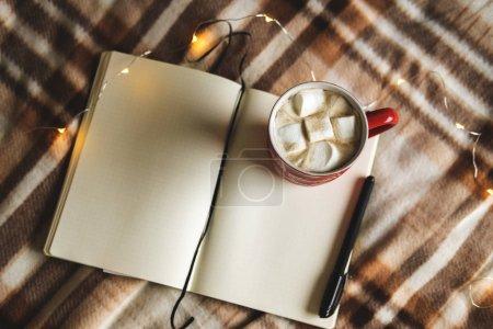 Jesienią i zimą tło z Notatnik, długopis, girlanda, kubek kakao, kawę lub gorącą czekoladę z Zefir na kratę. Koncepcja pracy, sporządzanie planów w ciepłe przytulne środowisko domowe.