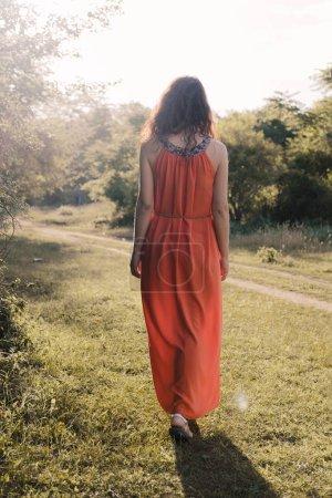 Photo pour Belle jeune fille aux cheveux frisés foncés en robe orange vif se promène au coucher du soleil à travers la forêt ou le champ. Humeur romantique. Solitude - image libre de droit