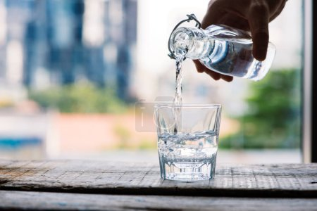 Photo for Hand poring clean drinking water into glass on wooden table - Royalty Free Image