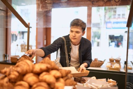 Photo for Handsome man with tray at bakery store buying buns - Royalty Free Image