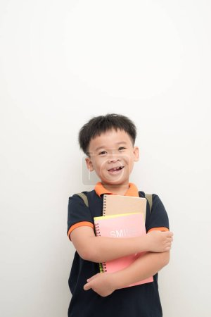 happy male elementary pupil holding books