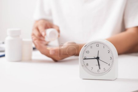 Doctor hand holding herbal medicine pill with clock and bottle, medical time concept