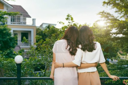 Outdoor fashion portrait of best girl friends posing back and hugs, both wearing stylish trendy hipster retro dresses. Enjoy their friendship and great time together.