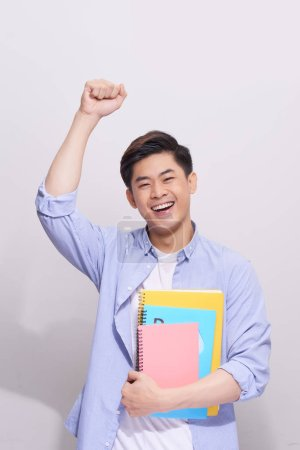 Happy handsome asain male student with books