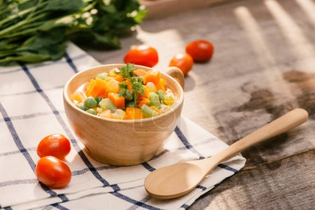Ladle of steamed freshly harvested young vegetables including crinkle cut sliced carrots, peas and potato for a healthy accompaniment to dinner