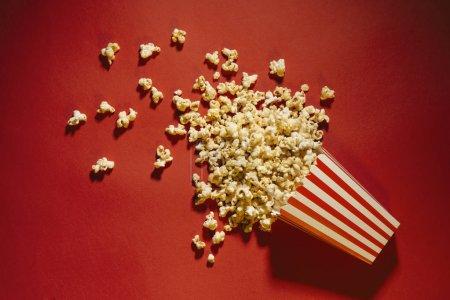 Photo pour Pop-corn déversé sur un concept de fond, de cinéma, de films et de divertissement rouge - image libre de droit