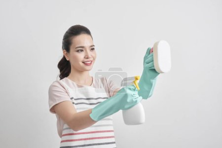 Young woman holding group of cleaning supplies. Household equipment, spring-cleaning, tidying up, cleaning service concept