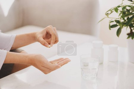 Hand takes yellow capsules of omega 3, white pills of glucosamine and calcium on plastic box, glass with water at wooden table, top view.