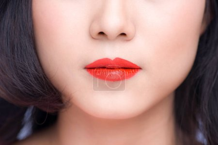 Macro of woman's face part. Red lips makeup.