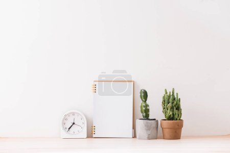 Photo for Empty notebooks on a white background with a cactus,  a white alarm clock - Royalty Free Image