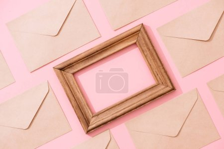 Frame from envelopes and postcard on pink table top view.