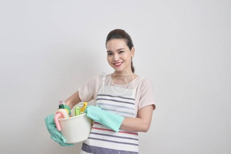 Cleaning services concept. Young cheerful woman holding bucket with detergents and rags at white isolated background. Household and home cleaning