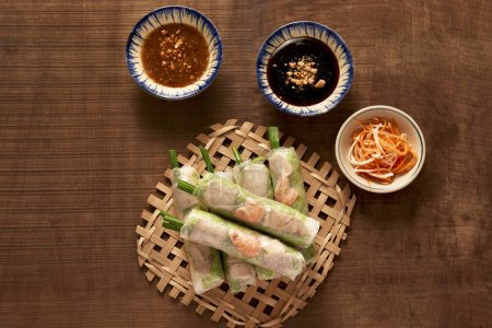 Vietnamese spring rolls - rice paper, lettuce, salad, vermicelli, noodles, shrimps, fish sauce, sweet chili, soy, lemon, veletables. Copy space. Asian and Vietnam food. Traditional national cuisine