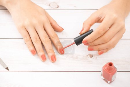 Nail care and manicure. Beautiful female hands applying pink nail polish.