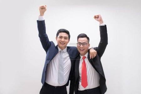 Successful Asian businessmen standing with hands up