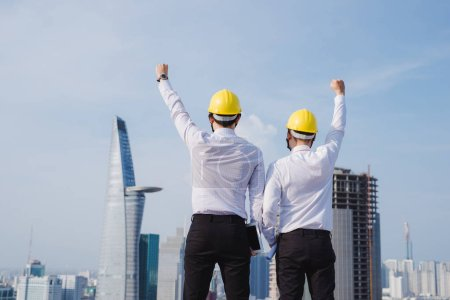two male engineers standing with hands up in construction site