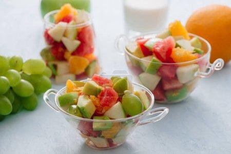 Foto de Trozos de frutas tropicales en un vaso. Rodajas de naranja, manzana, rebanadas de sandía en un tazón de vidrio. Frutas cítricas - Imagen libre de derechos
