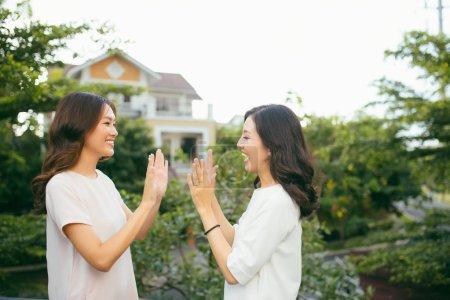 Two beautiful young women giving high five having fun outdoors