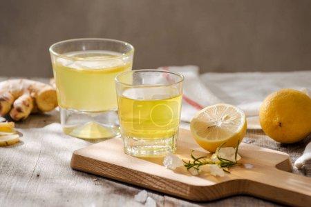 Photo pour Thé au gingembre avec citron et romarin dans une assiette, concept de boisson saisonnière - image libre de droit