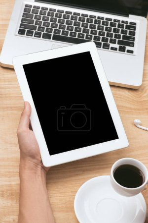 Photo for Human hands holding black tablet pc with blank screen and coffee cup on wooden table - Royalty Free Image