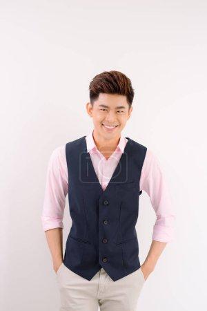 Photo pour Portrait de bel homme asiatique debout et souriant sur fond gris - image libre de droit