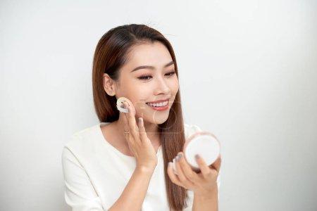 Photo pour Portrait de jeune femme, mettre la poudre pour le maquillage avec coussin cosmétique sur la peau du visage - image libre de droit