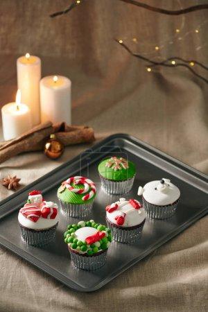 Photo pour Décoration de Noël sur cupcakes sur plateau avec des bougies sur fond - image libre de droit