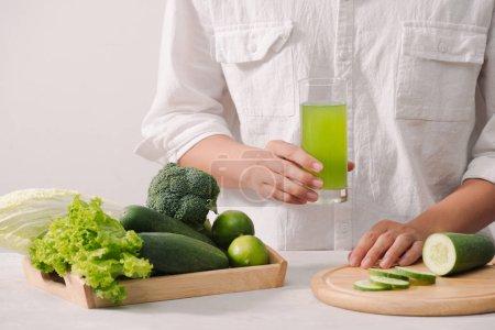 Photo pour Main de l'homme tenant le verre de jus de légumes fraîchement pressé avec des ingrédients sur planche de bois - image libre de droit