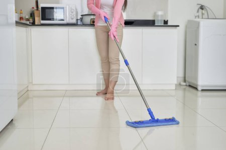 Photo for Housekeeping and cleaning concept, Happy young woman in pink rubber gloves wiping dust using mop while cleaning on floor at home. - Royalty Free Image