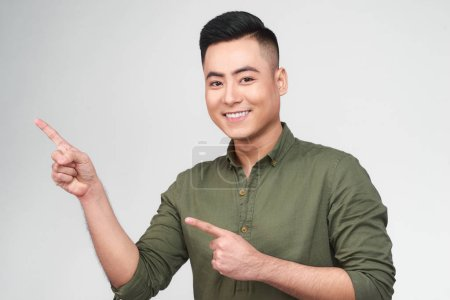 Photo for Happy excited man pointing away at copy space with two fingers isolated over white background - Royalty Free Image