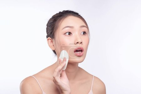 Photo for Woman with surprised face putting on make up, applied liquid foundation on her face - Royalty Free Image