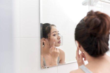 Photo pour Soins de la peau. Femme appliquant de la crème de peau sur son visage devant le miroir - image libre de droit