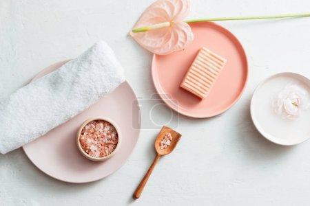 Photo pour Vue de dessus du spa avec savon, serviette, sel et fleur sur fond blanc - image libre de droit