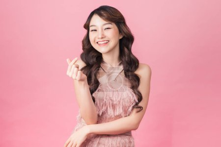 Photo for Image of charming woman 20s wearing dress smiling and standing isolated over pink background - Royalty Free Image