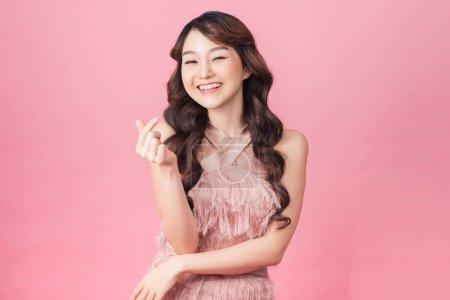 Photo pour Image de charmante femme 20s portant robe souriante et debout isolé sur fond rose - image libre de droit