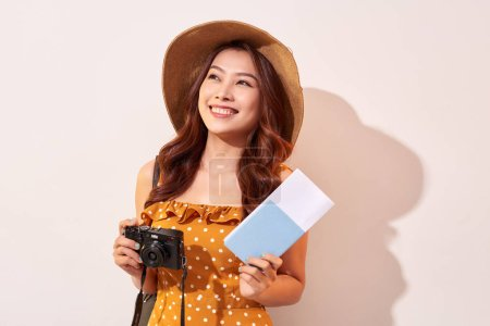 Photo for Expressive tourist woman in summer casual clothes, hat holding passport, tickets isolated on beige background. Female traveling abroad to travel weekends getaway. Air flight journey concept - Royalty Free Image