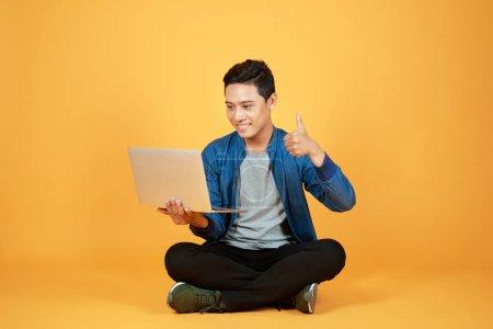 Photo pour Happy heureux homme asiatique tenant portable et levant son bras vers le haut pour célébrer les succès ou les réalisations. - image libre de droit